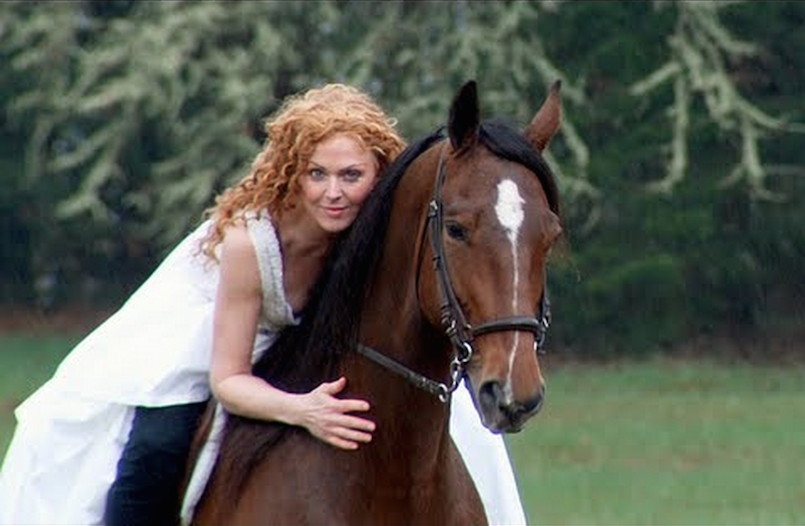 woman riding a horse in wedding gown