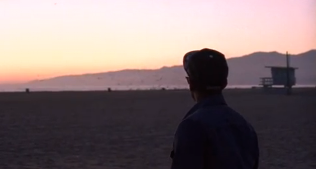 man standing on a beach at sunset