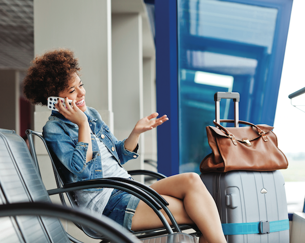 women talking on the phone in an airport with suitcase