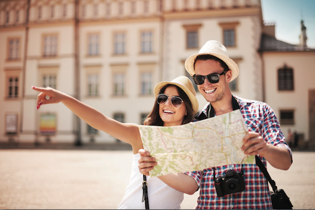 couple holding map and woman pointing