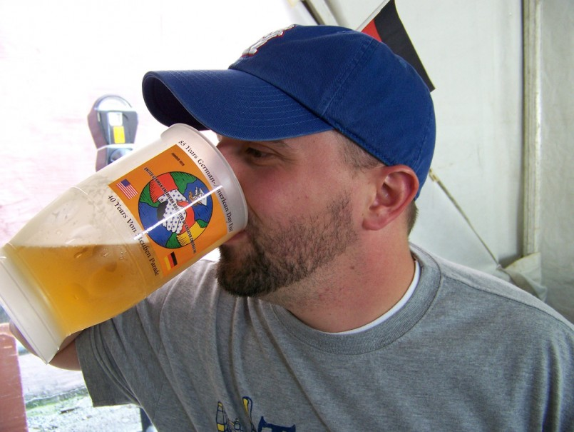 man with hat and facial hair chugging beer