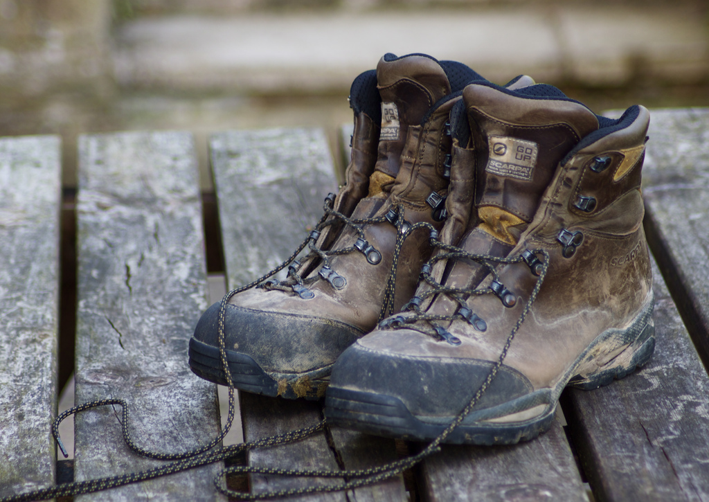 old hiking boots on wood deck