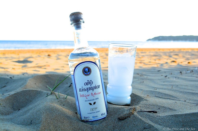 Ouzo in glass and bottle on beach