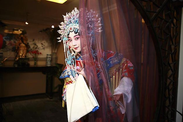chinese woman in costume staring from behind sheer curtain