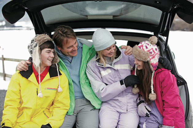 family sitting in back of suv in snow gear