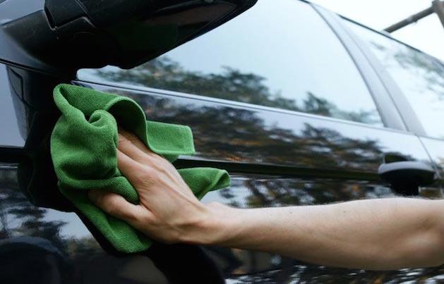 person waxing a car