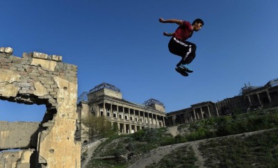 young afghan boy doing parkour on ruined building