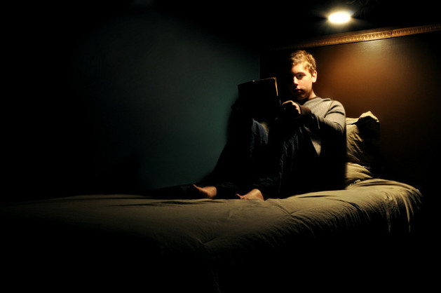 young boy reading in dark bed
