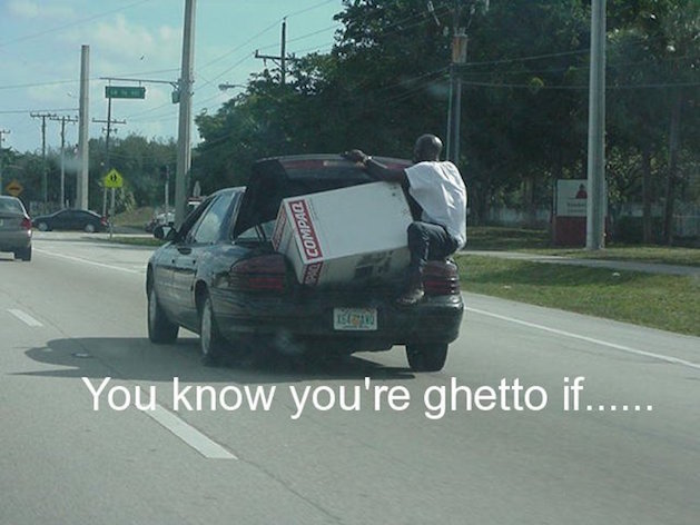 man riding in trunk of car in the ghetto