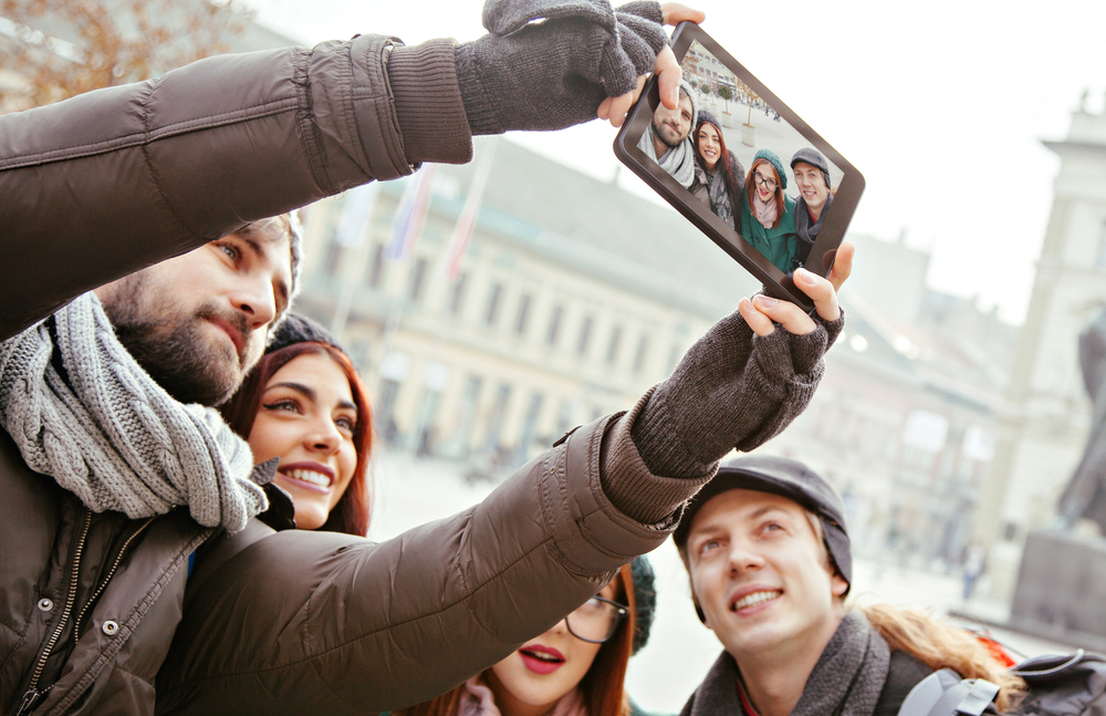 Group Of Cheerful Tourists Taking Selfie Using Digital Tablet