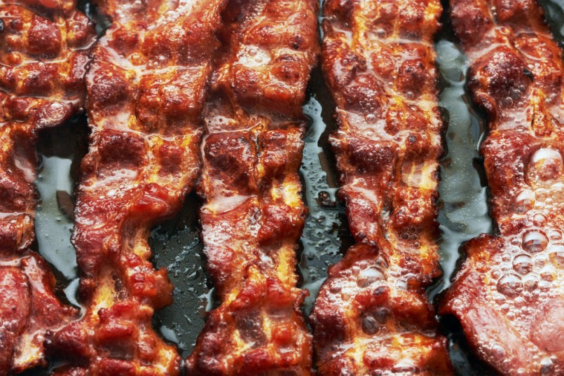 Bacon slice being cooked in frying pan