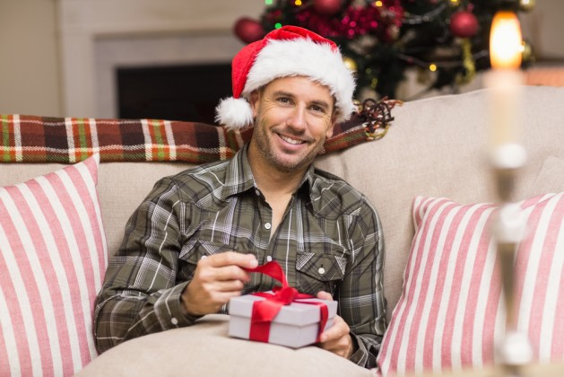 Happy man in santa hat opening a gift at home in the living room