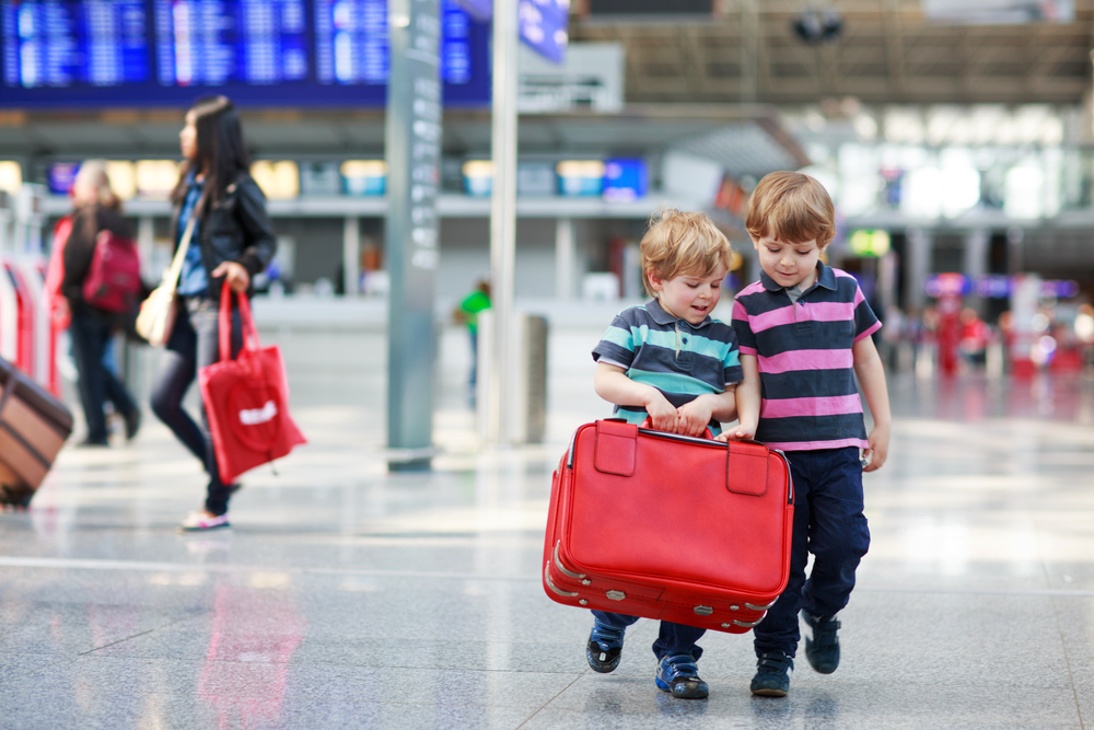 Two little sibling boys having fun and going on vacations trip with suitcase at airport