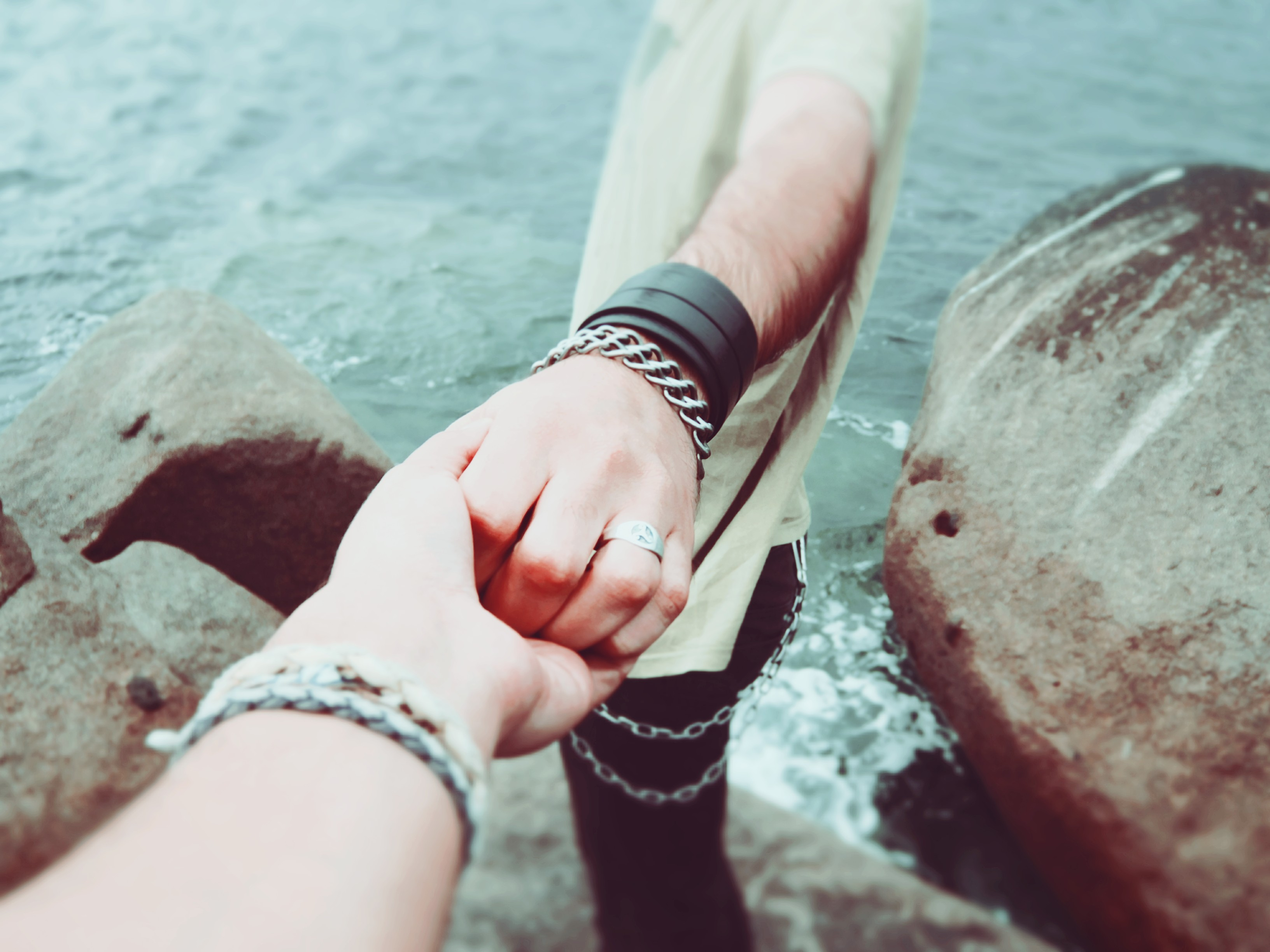 man and woman holding hands on rocks by ocean