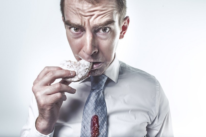 man eating jelly donut doughnut with jelly on his tie