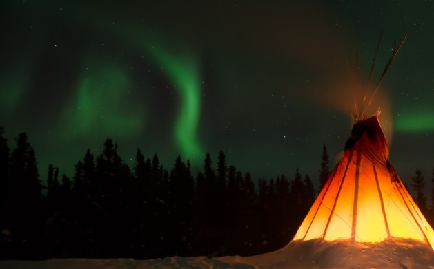 Traditional native dwelling in the far north with northern lights in the sky