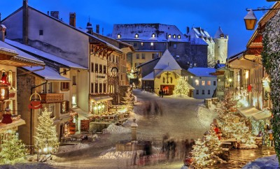 Winter (Christmas) in the medieval town of Gruyeres, Fribourg canton, Switzerland. In the background looming over is the Chateau de Gruyere