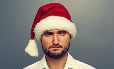 sad man in santa hat over dark background