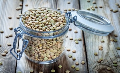 glass jar with organic green lentils on wooden background