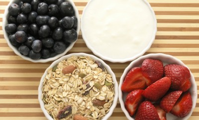 ingredients of a healthy tasty breakfast- blueberries, strawberries, muesli, and yogurt