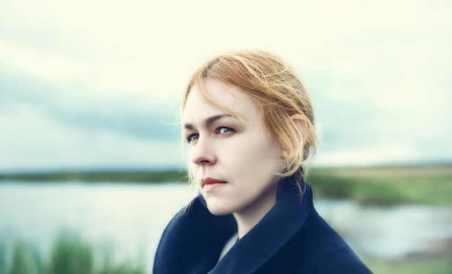 Portrait of attractive young woman on countryside with a sad expression