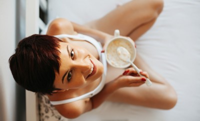 Woman having breakfast in bed. Healthy breakfast of cereals and milk. Caucasian woman smiling looking at camera. Top view