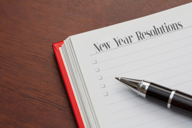 Conceptual,notebook on a wooden table. open diary and pen with new year resolutions words