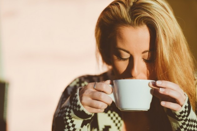 woman sipping hot liquid from white mug