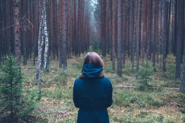 woman standing in forest looking at trees alone
