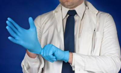 Medicine doctor putting on protective gloves before examination isolated on blue background