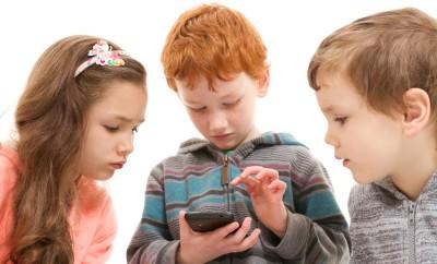 Three children watching child using smartphone. Isolated on white.