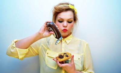 Young Woman Pouring Chocolate Sauce Over Chocolate Chip Cookie