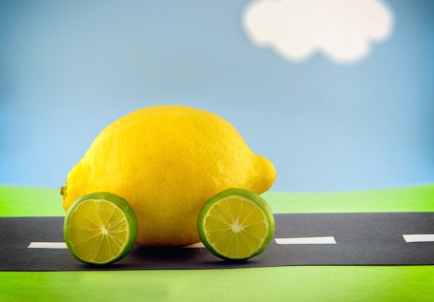 A lemon car with lime wheels driving along a construction paper scene