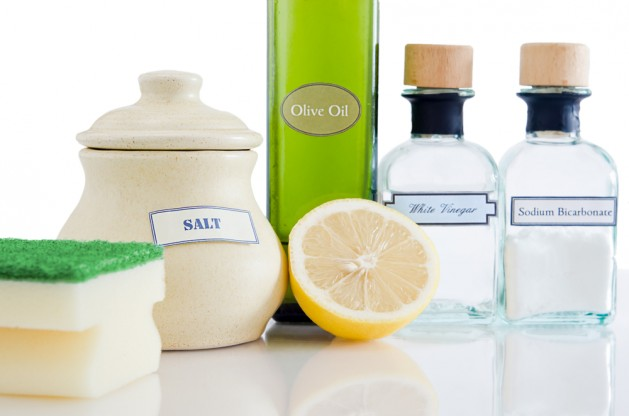 A range of natural, non-toxic cleaning products in containers on a shiny reflective surface with a white background