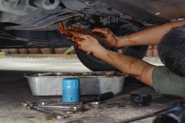 Car mechanic loosen oil filter