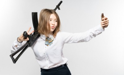 Girl with a Kalashnikov in his hand makes selfie. Isolated