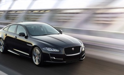Jaguar XJ in black driving on bridge