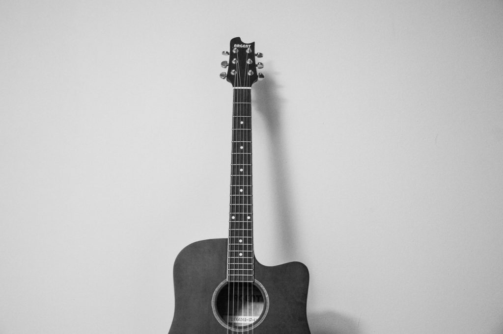 black and white photo of acoustic guitar leaning against a wall