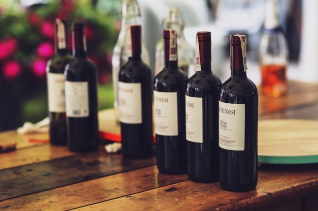 six bottle of red wine on reclaimed wood table