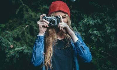 young blond woman in forest taking a photo looking at the camera