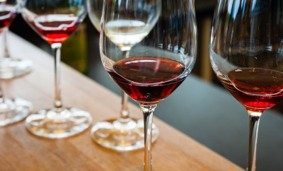 Detail of wine glasses with red wine samples, on wood counter with other glasses in background