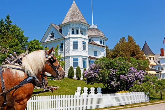 The Wedding Cake Cottage is shown on the West Bluff on Michigan's Mackinac Island. A horse stands in front and the lilacs out front are in full bloom