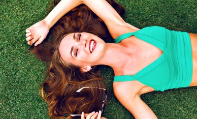 Summer close up portrait of pretty smiling young woman, laying on the grass, enjoy her vacation, natural make up long brunette hairs, joy. happiness