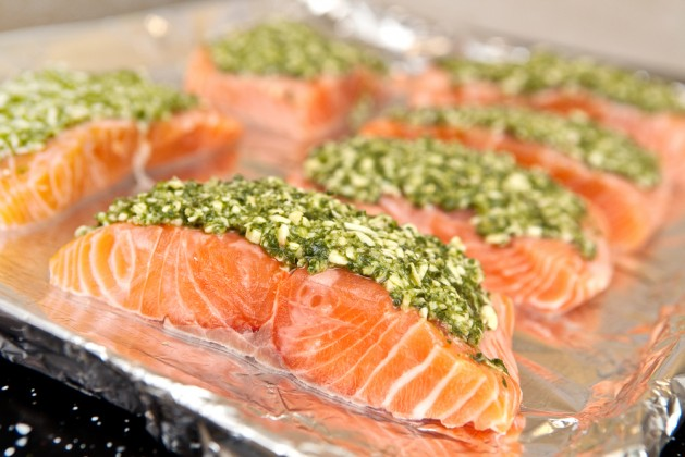Fresh slices of salmon fish with basil pesto and parmesan on baking tray