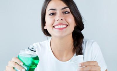 Portrait of beautiful girl using mouthwash. Isolated on white