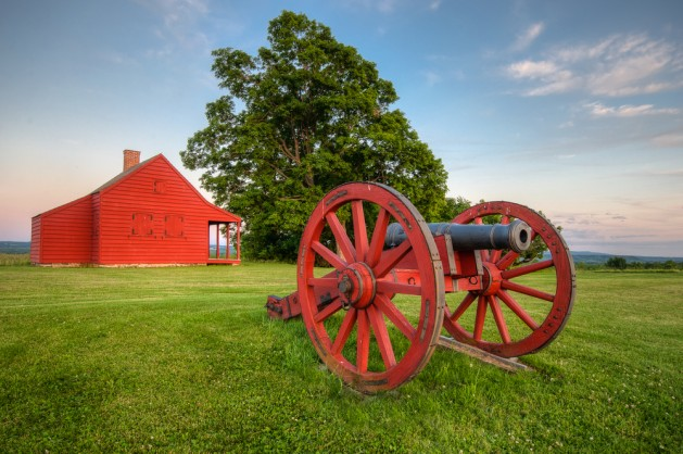 Cannon at Saratoga National Battlefield with Neilson Farm in the background