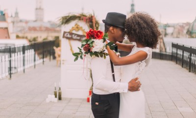 Happy black wedding couple softly hugging on the rooftop during the wedding ceremony