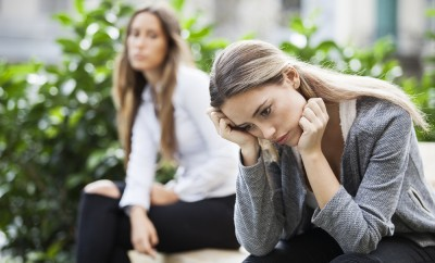 Portrait of young woman and friend outdoor on street having problems. Depression concept