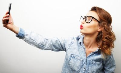 Pretty hipster girl taking selfie