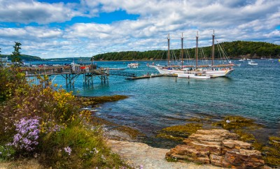 Rocky coast and view of boats in the harbor at Bar Harbor, Maine